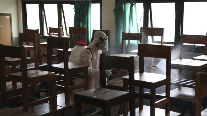 A member of Indonesia Red Cross sprays disinfectant in an attempt to help curb the spread of the new coronavirus inside a classroom at a school in Jakarta, Indonesia Tuesday, June 9, 2020.