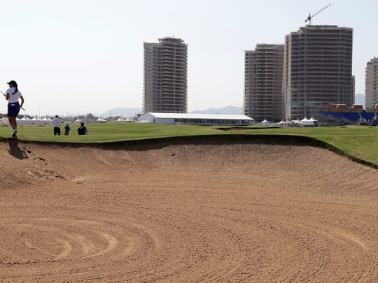 Brazil's Victoria Lovelady, left, walks out of a sand trap on the seventh fairway during a golf practice round at the 2016 Summer Olympics in Rio de Janeiro, Brazil, Friday, Aug. 5, 2016. (AP Photo/Charlie Neibergall)