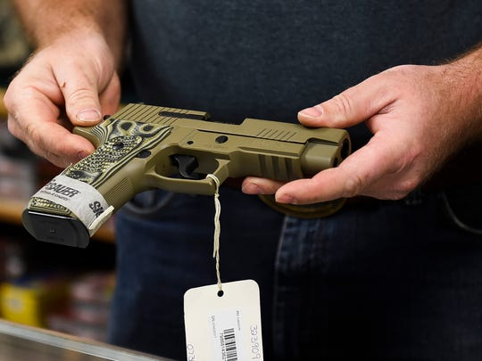 Tony Duda helps a customer pick out a gun at Rocky Mountain Shooters Supply in Fort Collins in this file photo. Gun-control measures continue to carry considerable weight in how the Colorado Legislature sets state policy.