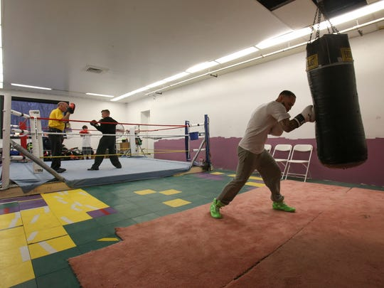 Joey Tiberi works a punching bag (right) as his father Joe Tiberi, trains with boxer Ryan Douglas in the boxing gym run by the elder Tiberi in the Delaware Swim and Fitness Center in Pike Creek.