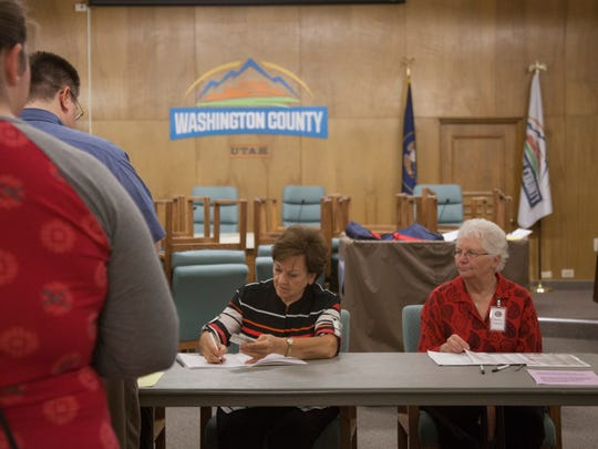 Poll workers at the Washington County Administration Building verify voters Tuesday, June 26, 2018. Six Washington County voting locations will be open for the general election.