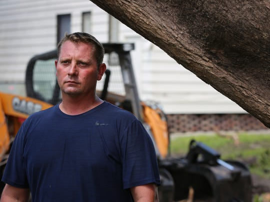 David Nagel, 38, helped organize a group of 12 people to drive to Naples from Minnesota to provide relief from destruction caused by Hurricane Irma. He was inspired by an article he read about a tree that fell onto a woman's home and punctured the roof. Here, he stands beneath that same tree.