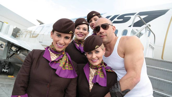 "Vin Diesel poses with the cabin crew of the ""Fast & Furious 777."""