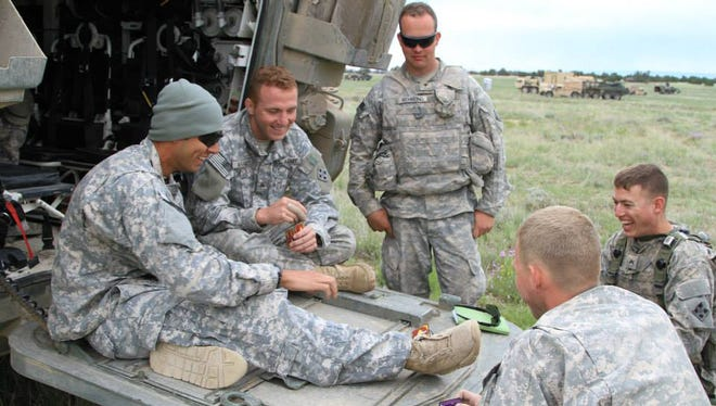 Soldiers with 1st Brigade, 4th Infantry Division from Fort Carson take a break during training. Their uniforms are without combat patches and badges.