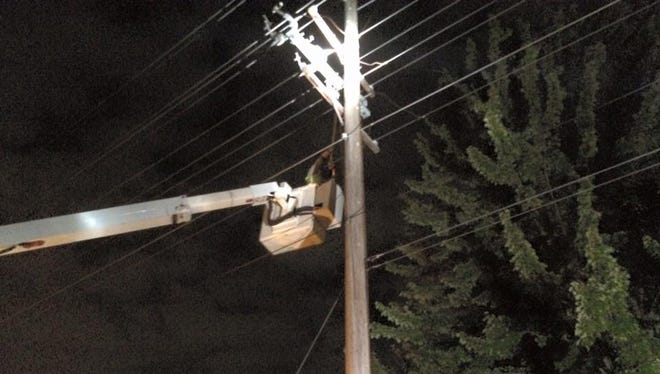 A Wisconsin Rapids Water Works & Lighting Commission lineman works on power lines off Gaynor Avenue on Tuesday evening.