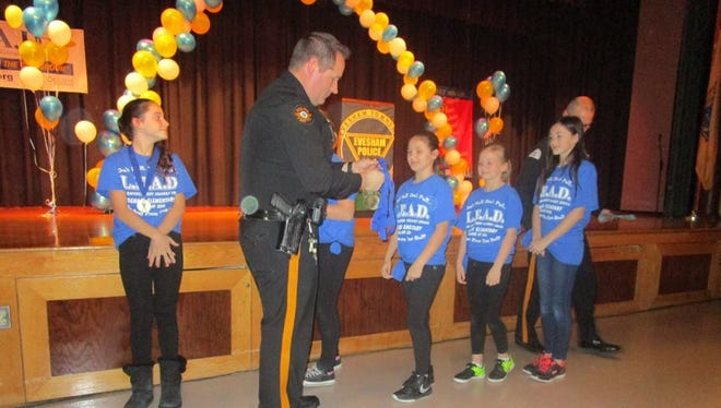 Evesham police officer Michael Trampe congratulates Evesham students who graduated from the L.E.A.D. program course recently.