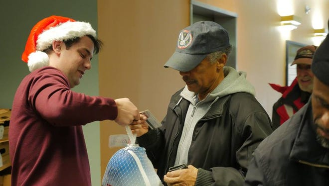 Tyler Patterson Esq. of the Tully Rinckey PLLC Binghamton office hand-delivers a turkey to an appreciative veteran.