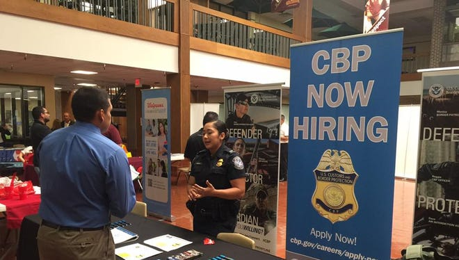 A U.S. Customs and Border Protection agent discusses job openings at an Ysleta Independent School District-sponsored job fair Saturday.