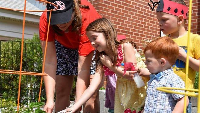 Kids help Cara Fleischer release 10,000 ladybugs into Saint Paul's garden to control pests organically.