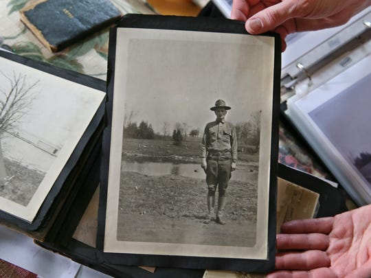 Sue Ellen Windsor looks over a diary and photo albums kept by her grandfather, J. Earl Windsor, during his time in Rochester during WWI when he was a student at the Aerial Photography School at Eastman Kodak, Tuesday, May 23, 2017, at her Penfield home.  This photo of her grandfather was taken in 1918 during training with the Army in Sackets Harbor, NY.