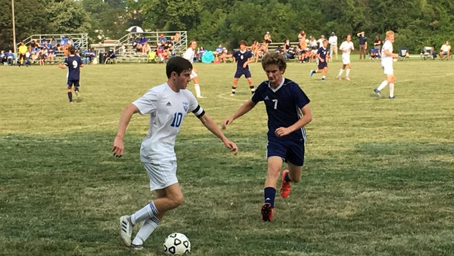 Washburn Rural senior Ethan Hensyel (10) advances the ball against Hayden's Michael Sandstrom (7) in the Junior Blues' 3-0 win over the Wildcats Thursday at Hayden.