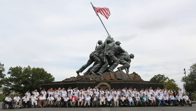 Veterans from World War II, Korean and Vietnam Wars salute during a group photo at the Iwo Jima Monument in Washington, D.C. The Honor Flight Bluegrass chapter flew the veterans to the Capitol to visit the war memorials. Sept. 21, 2016.