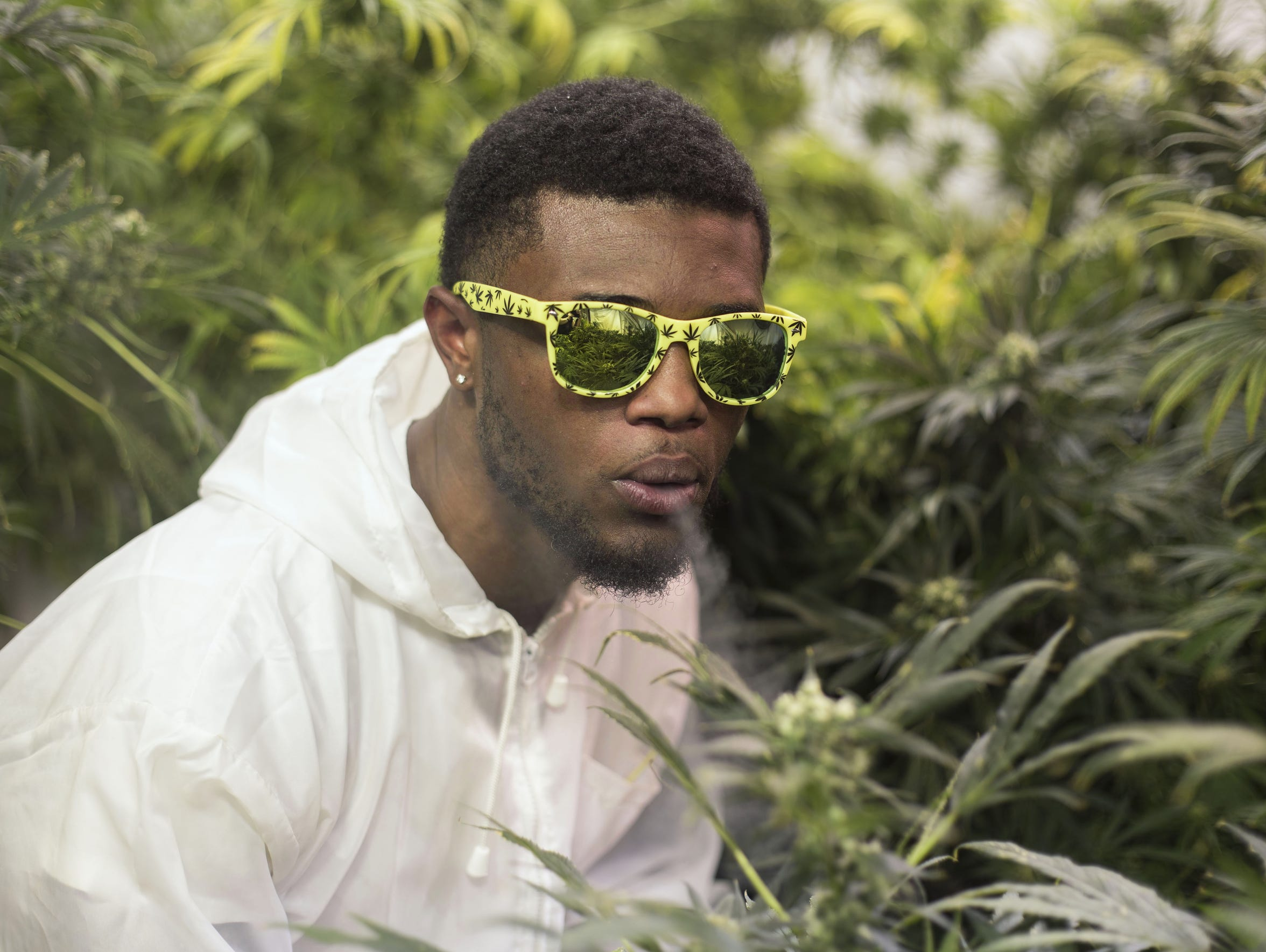 Treyous Jarrells blows smoke from his joint in his