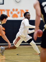Northeastern's Fred Mulbah drives against Delone Catholic