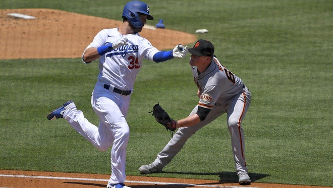 Los Angeles Dodgers' Cody Bellinger, left, tries to avoid being tagged out by San Francisco Giants starting pitcher Logan Webb as he runs to first during the first inning of a baseball game Saturday, July 25, 2020, in Los Angeles.