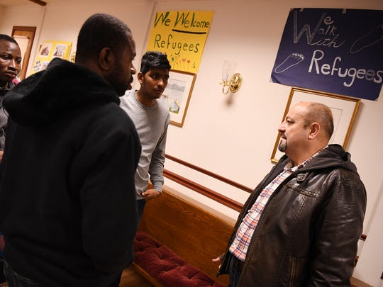 (from right) Samer Albahri, a refugee from Syria, talks