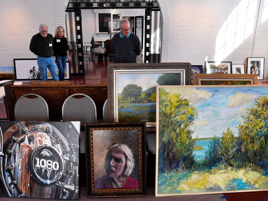 Juror Randy Bacon looks over a collection of the selected works from the 20th annual Stars of Texas Juried Art Exhibit. Behind him, Charles Stavley and Nesa Morelock stand by to assist, Saturday Jan. 27, 2018 at Brownwood's Depot Civic & Cultural Center. Bacon selected 97 works out of 347 entries. The show ends Feb. 17.