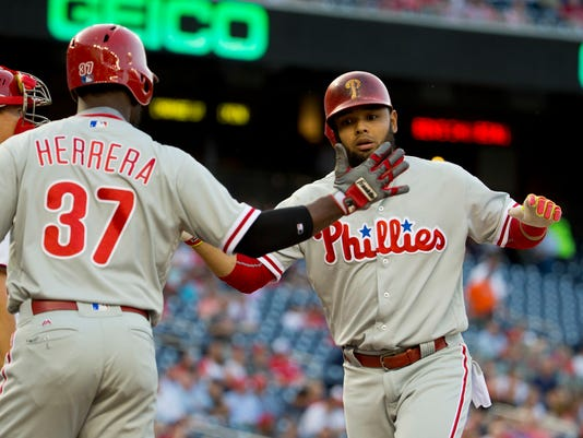 Philadelphia Phillies Andres Blanco is greeted at home by teammate Odubel Herrerra after hitting a two-run homer off Washington Nationals starting pitcher Max Scherzer (31) during the first inning of a baseball game, Tuesday, April 26, 2016 in Washington. (AP Photo/Pablo Martinez Monsivais)