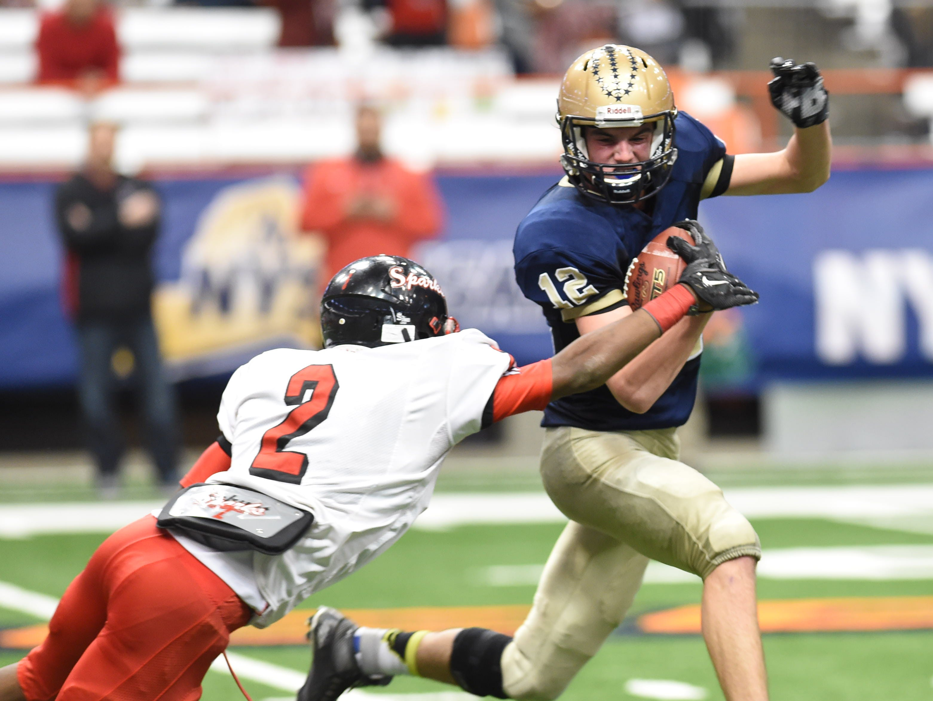 Lourdes' Luke Timm carries the ball away from South Park's Daryl Moore during the New York State Championship final in Syracuse on Friday.
