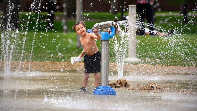 Levi Shorter, 4, takes aim with a water canon while playing at the Lake George splash pad in 2015. Splash pads and wading pools are starting to open in the St. Cloud area.