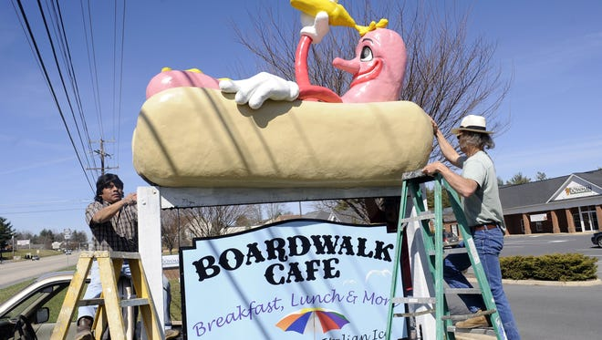 """Assistant Sergio Gomez helps artist Mark Cline in mounting Cline's 8-foot hotdog creation atop the sign for Boardwalk Cafe as the restaurant's new """"mascot"""" visible from U.S. 250 just outside Waynesboro on Wednesday, March 17, 2010. Not counting time to sketch the design, the creation took Cline about a week to construct."""