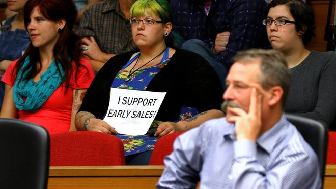 Supporters for marijuana sales hold signs during a City Council meeting where the discussion of early sales was a hot topic, Monday, August 31, 2015, in Salem, Ore.