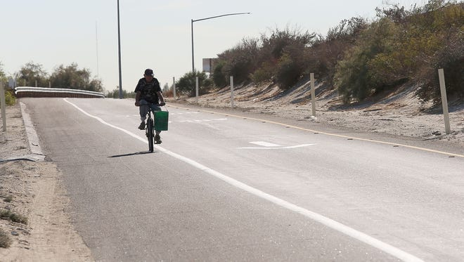 A cyclist rides on the shoulder of the Dillon Road Interstate 10 off-ramp in Indio near where the CV Link is planned.