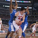 Kentucky's Dakari Johnson, left, and James Young pressure Wisconsin's Frank Kaminsky during the semi-final game Saturday night at the Final Four at AT&T Stadium in Arlington, Texas. April 5, 2014