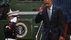 President Obama salutes a U.S. Marine as he steps off
