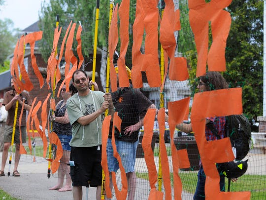 Tim Novack, of Wayne, Mich., holds a protest banner Wednesday, May 25 at the Marysville City Park near the Coat Guard's oil spill exercise. Novack is with the Michigan   Coalition Against Tar Sands.