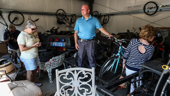 Det. Shane Stewart stands inside the 5th Precinct garage as Highlands residents look for their property, which was recovered by police.  LMPD has recovered dozens of yard items -- from gnomes, birdbaths, lawn ornaments as well as bicycles and a trailer -- which were stolen over a period of a few weeks from Highlands residents. The department's 5th Division, where property is being held, is located at 2301 Douglass Boulevard. Here's when you can view and recover the property: 