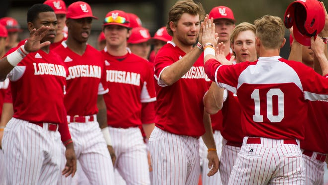 Ragin Cajuns' Brad Antchak (10) is greeted by teammates after scoring against the Sam Houston State Bearkats in the fifth inning at Tigue Field.