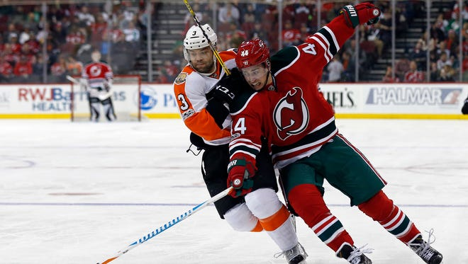 New Jersey Devils left wing Miles Wood (44) battles for the puck with Philadelphia Flyers defenseman Radko Gudas (3) during the second period of an NHL hockey game, Thursday, March 16, 2017, in Newark, N.J.
