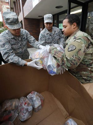 Members of the New York Air and Army National Guard unload bags of food at the New Rochelle Community Action Partnership, at the WestCOP building in New Rochelle, March 12, 2020