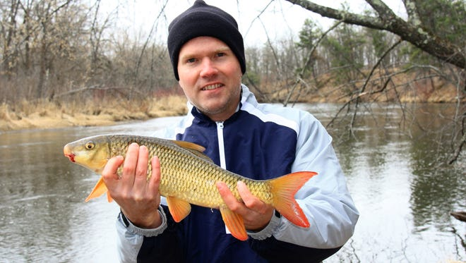 Jesse Simkins of Colorado holds a redhorse sucker he caught while visiting family in Minnesota.