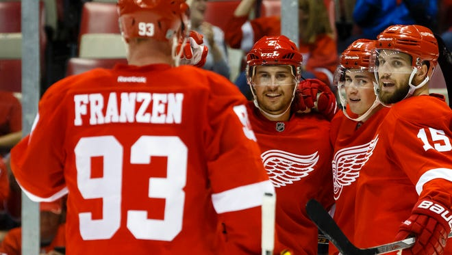 Red Wings center Dylan Larkin receives congratulations from teammates after scoring in the first period of the 6-1 win over the Penguins in an exhibition Thursday at Joe Louis Arena.