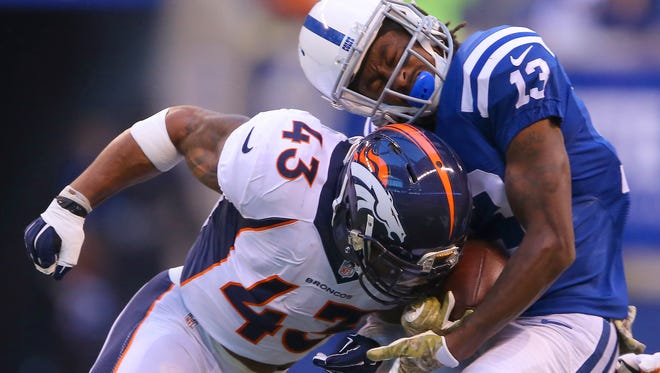 Indianapolis Colts wide receiver T.Y. Hilton (13) is hit hard by Denver Broncos strong safety T.J. Ward (43), who was called for a penalty on the play during the first half of an NFL football game Sunday, Nov. 8, 2015, at Lucas Oil Stadium.