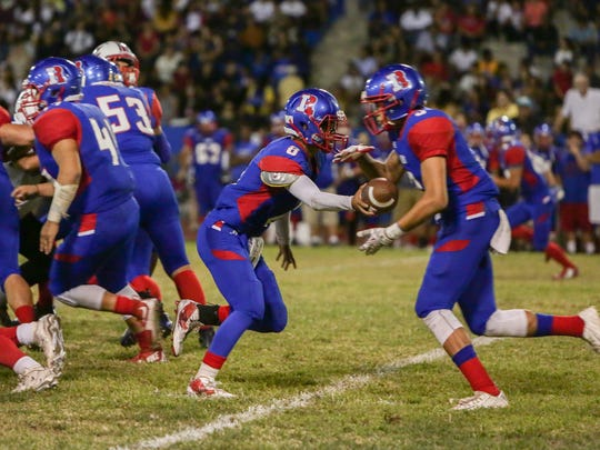 Dimitri Long of Indio High School hands off the ball to Isaac Scott during Friday night's DVL opener against Palm Springs.