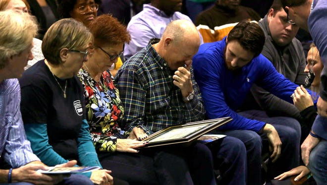 The family of Collin Rose, the Wayne State University police officer who was killed in the line of duty in late November 2016, looks over the framed diploma that WSU president M. Roy Wilson had just given fiancé Nikki Salgot during graduation ceremonies at the Matthaei Physical Education Center on the campus of Wayne State University in Detroit.