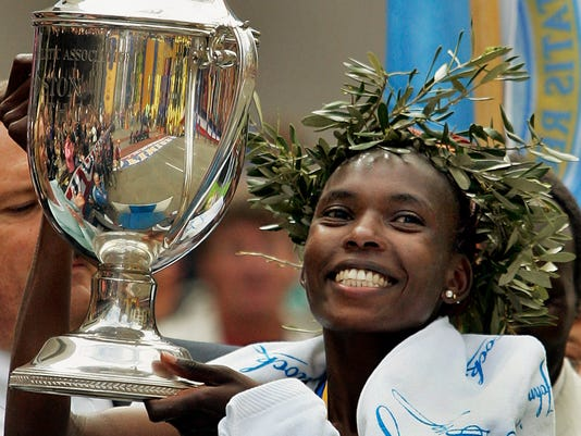FILE - In this Monday, April 17, 2006, file photo Rita Jeptoo of Kenya holds the trophy after winning the women's division of the 110th running of the Boston Marathon, in Boston. Kenyan police investigating doping searched the hotel rooms of two Italian athlete managers during the Kenyan Olympic trials, and questioned the two men at police headquarters on Monday July 4, 2016.  The agents, Federico Rosa and his father, Gabriele, represent a number of top Kenyan athletes and previously represented marathon runner Rita Jeptoo, one of the highest-profile Kenyans to be banned for doping. (AP Photo/Elise Amendola, FILE)