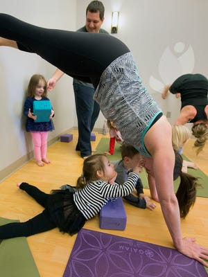 Ashley Warren, age 3, bottom, of Springettsbury Township, touches her mother Erica's nose during family Yoga at Evolution Power Yoga Sunday February 28, 2016 in York Township