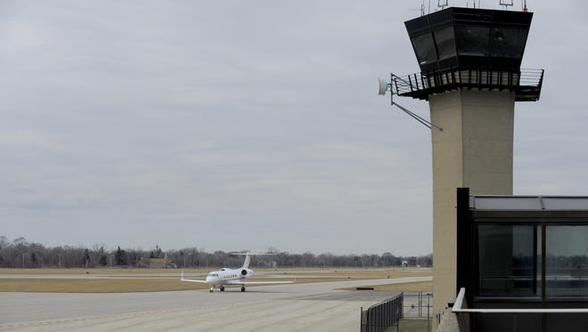 A plane taxis past the Detroit City Airport tower in this file photo from Friday March 20, 2015.