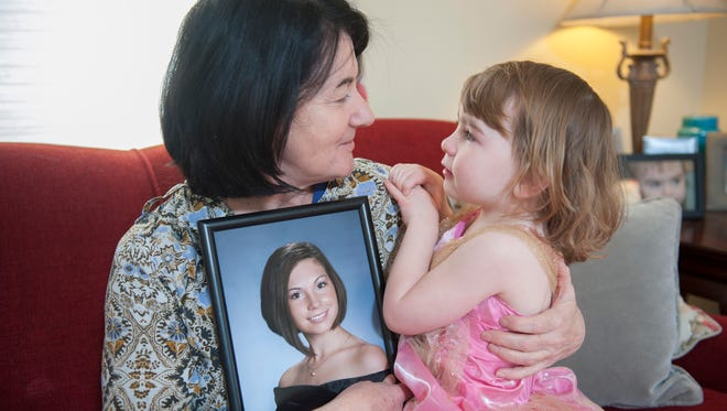 Denise Urevick holds her granddaughter Lilly Doto, 4, and a picture of her daughter (Lilly's mother) Caitlin Kearney. The Pitman native has been missing for over 2 years and the case has gone cold.