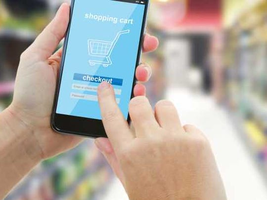 Person using an app to shop online while in a store.