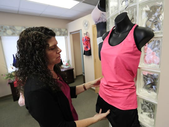 Nell's Wigs & Boutique owner Stacey Nellen-Kolze adjusts
