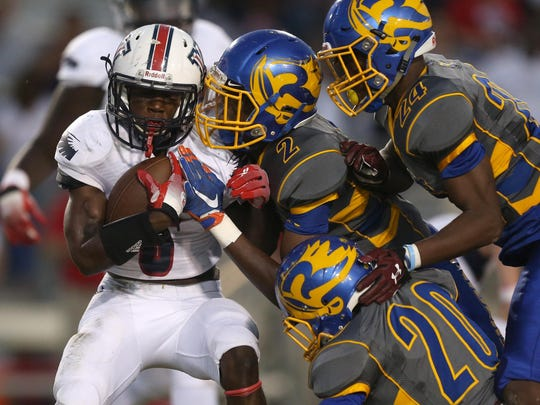 Wakulla's Cephus Greene is gang-tackled by Rickards' Javon Peterson (2), Anfernee Simmons (20) and Tavyn Jackson (24) during their game at Cox Stadium on Thursday night.