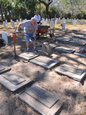 Jim Braun and Marcia Jimenez clean up around the cremated grave sites at the Brevard County Veterans Cemetery in Titusville.. A group named Friends of the Cemetery held a cleanup Wednesday at cemetery.