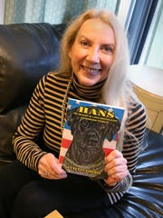Author Lynette Loomis with the book she wrote about Hans, the kill shelter puppy that was taken in by veterans at the Veteran Outreach Center's Richards House in Rochester.