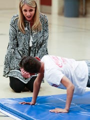 David Harrison Elementary School Principal Chris Parker talks with Uzziah Huskisson, 8, as he does push-ups in PE class on Tuesday, March 6, 2018.