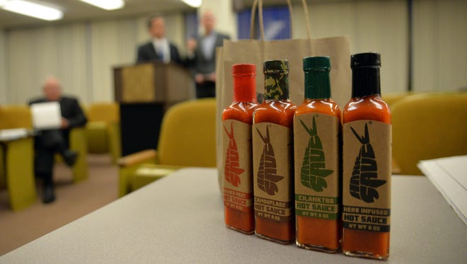 Hank Sauce co-owner Josh Jaspan (right) and attorney Steve Fabietti address the Millville Planning Board about the company's major site plan application, as bottles of the hot sauce are displayed on a table.